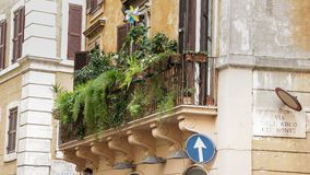 Balcony with flowers  in Rome. Balcony with flowers on an old yellow apartment building in Rome Royalty Free Stock Photos
