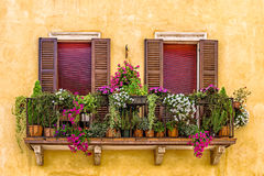 Balcony with flowers in Verona. Balcony with closed beautiful windows colored with flowers in Verona Stock Images