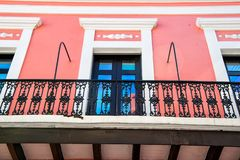 Balcony and glass windows in San Juan, Puerto Rico. Balcony with decorative metal railing and glass windows in black frames on pink plastered wall background in Stock Photography