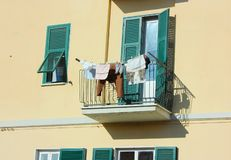 Terrace is used to hang clothes in a normal family home. Balcony of a house with ocher-colored walls. the terrace is used to hang clothes in a normal family royalty free stock photo