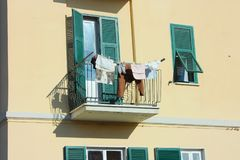 Terrace is used to hang clothes in a normal family home. Balcony of a house with ocher-colored walls. the terrace is used to hang clothes in a normal family stock photos