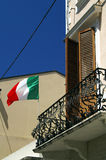 Balcony and Italian flag. Italian flag flying by balcony on old building Stock Images