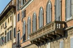 Balcony of Italian House. Ancient Roman stone balcony and row of windows of Italian building stock image