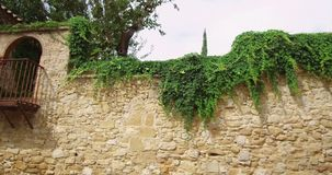Balcony in a medieval stone wall. Balcony in a medieval stone wall with lush vegetation that overflows.Tracking shot left stock video footage