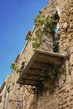 Balcony on old stone house. Low angle view of fig tree on balcony on old stone house, Poggioreale, Sicily royalty free stock image