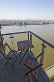 Balcony with outdoor furniture and river views. Balcony over river thames with amazing city views and outdoor wooden furniture stock photography