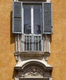 Balcony in Rome. Small balcony with wooden shutters and a bas-relief in Rome, Italy Stock Images