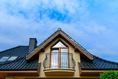 Balcony and roof with tiles of single family house. Against blue sky stock images