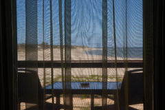 Balcony with sea view. A balcony with coffee table and chairs through a net curtain, overlooking a beach and the sea on a hot day Royalty Free Stock Images