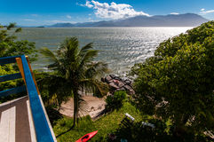 A balcony and a small beach. A chair, a white bench, a red kayak and a palm tree on a small beach seen by a balcony. In Florianopolis, Santa Catarina State Royalty Free Stock Photography