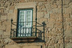 Balcony on a stone wall from old building at Guarda. Balcony with wrought iron railing and glazed door on a stone wall from old building, in a sunny day at stock photography