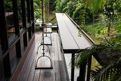 Balcony with swing chair near park. Balcony with Relax swing chair near wooden table near canal and summer plant and park Stock Photo