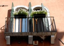 Balcony with symmetries of windows and flowers in Venice. Stock Photography