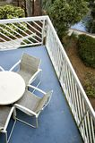 Balcony with Table and Chairs and Lush Foliage below. Partial view of balcony from above with table and chairs and lush foliage and pond below Stock Photo