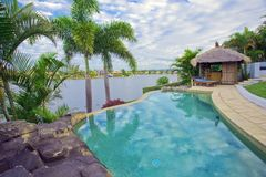 Balcony views from waterfront Mansion. Overlooking the pool, canal and Bali hut Stock Image