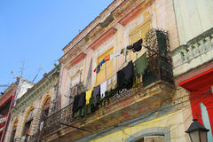 Balcony with wet clothes in Havana, Cuba. A typical old house in colonial style on central Havana, Cuba, wet clothes are drying in the wind, hanging in the Stock Image