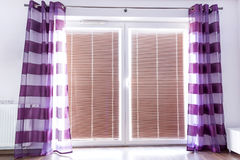 Balcony window with purple curtains stock images