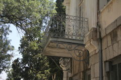 Balcony with wrought iron railings twisted on the old dilapidated wall closeup Royalty Free Stock Photo