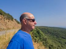 Bald aged man in sunglasses looks into the distance in perspective on the valley stock photo