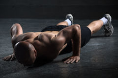 Bald athlete with a beautiful body and naked torso. Bald athlete with a beautiful body and a naked torso doing push-ups exercise on the floor. Studio shot in a Stock Image
