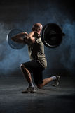 Bald athlete doing exercise with a barbell Stock Photos