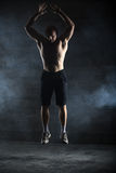 Bald athlete topless jumping up. The picture in the studio in the style of low-key royalty free stock image