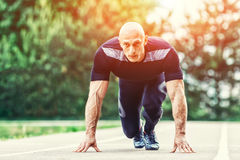 Bald Athletic Man in Running Start Position and Looking Into the Distance in stadium. Royalty Free Stock Image