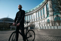 Bald bearded guy with black fix against building Stock Image