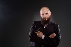Bald bearded man holding a pipe in crossed hands. Stock Photo