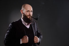 Bald bearded man holding a smoking pipe Royalty Free Stock Images