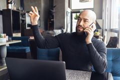 Bearded man sits in cafe at table in front of laptop, talking on phone and asking for waiter.Guy sits in restaurant,calls friends. Bald bearded man sits in cafe stock photo