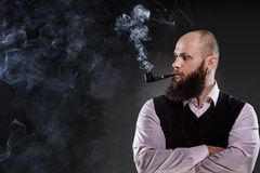Bald bearded man smoking a pipe Stock Image