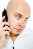 Bald, blue-eyed man with a telephone. Studio. isolated Stock Photo