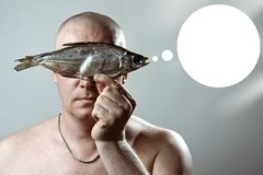 Bald brutal man with a bare torso holds a dried fish in front of his face