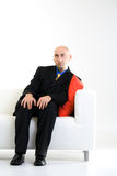 Bald Businessman on Chair Stock Images