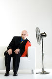 Bald Businessman with Fan. Bald businessman sits with a floor pedestal fan pointed in his direction.  He is sitting on a white chair and leaning against a red Stock Images