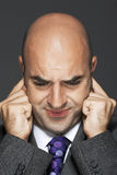 Bald businessman with fingers in ears making a face Stock Photography