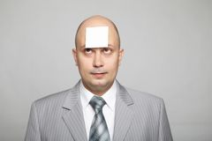 Bald businessman in a gray suit Stock Image