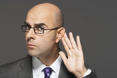 Bald Businessman With Hand Behind Ear. Closeup of a bald businessman with hand behind ear listening closely against gray background royalty free stock photos