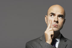 Bald Businessman With Hand On Cheek Thinking Stock Images