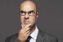 Bald Businessman With Hand On Chin Making Funny Face Stock Photography