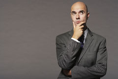 Bald Businessman With Hand On Chin Thinking Royalty Free Stock Photos