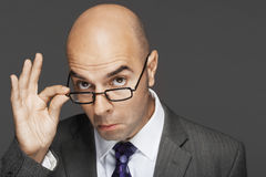 Bald Businessman With Hand On Glasses Making A Face Stock Images