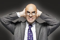 Bald Businessman With Hands Over Ears Looking Sideways Stock Image