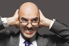 Bald Businessman With Hands Over Ears Looking Sideways Royalty Free Stock Photos