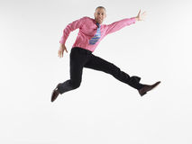 Bald Businessman Jumping Against White Background. Full length portrait of a bald businessman jumping against white background Royalty Free Stock Photo