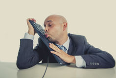 Bald businessman kissing computer keyboard with funny face expression Stock Photography