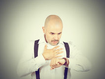 Bald businessman looks at his watch Stock Photography