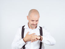 Bald businessman looks at his watch Royalty Free Stock Image