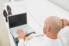 Bald businessman using laptop on sofa at home Stock Photos